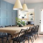 Dining room with blue paneled walls and long table with seating for up to 10 peo...