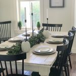 Simple and neutral thanksgiving tablescape with white dishes, black candlesticks...